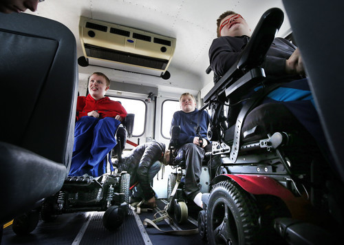 Joshua, left, Anthony, and Andrew Honey get help from their sister Jessica as their wheelchairs are strapped into a new bus in Pleasant Grove on Monday, Dec. 24, 2018.