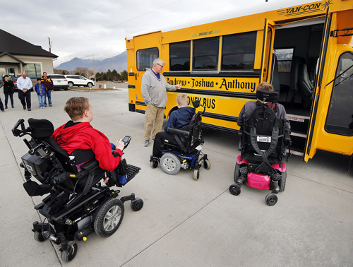 Joshua Honey, left, and his brothers Anthony and Andrew look at their new bus in Pleasant Grove on Monday, Dec. 24, 2018.