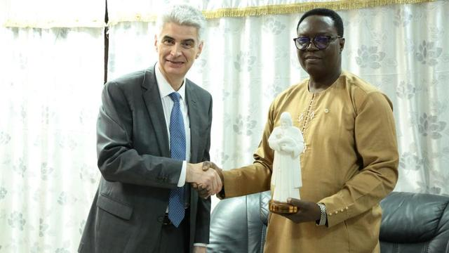 Presiding Bishop Gérald Caussé in a handshake with Orou Baro Mora, cabinet minister in the Ministry of Interior and Public Security in the Benin Republic, after the presentation of a gift from the Church.