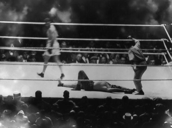 Argentine heavyweight champion Luis Angel Firpo lies knocked out by American world heavyweight champion boxer Jack Dempsey (1895-1983) at the end of their match at the Polo Grounds in New York, September 14, 1923. The bout lasted only 3 minutes and 57 seconds. (Photo by Topical Press/Hulton Archive/Getty Images)